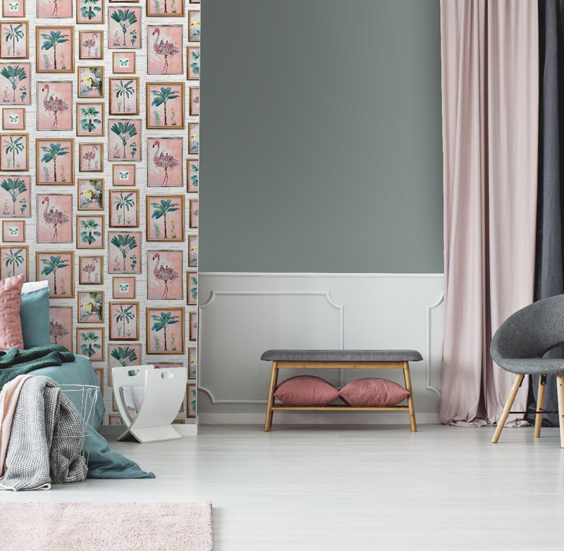 Grey armchair and posters in bedroom interior with green bed against leaves wallpaper